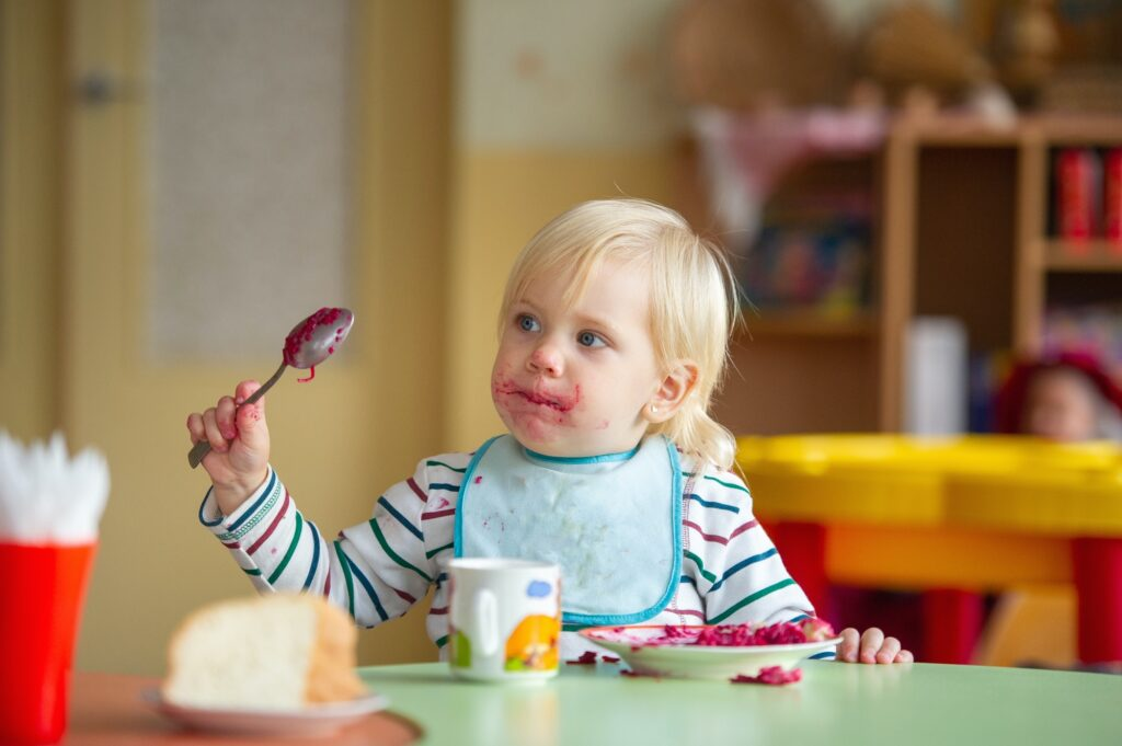 the child eats healthy food in kindergarten or at home and gets dirty